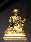 A Sino-Tibetan gilt bronze figure of a lama. 18th c.