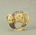 JAPANESE CARVED IVORY NETSUKE OF A MYTHICAL BEAST