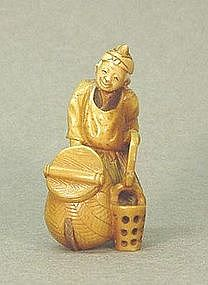 JAPANESE CARVED IVORY NETSUKE OF A MAN HOLDING BUCKET