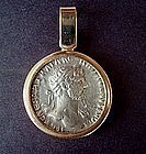 A ROMAN SILVER COIN OF EMPEROR HADRIAN SET IN 18K GOLD