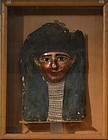 AN EGYPTIAN POLYCHROME AND GILT CARTONNAGE MUMMY MASK